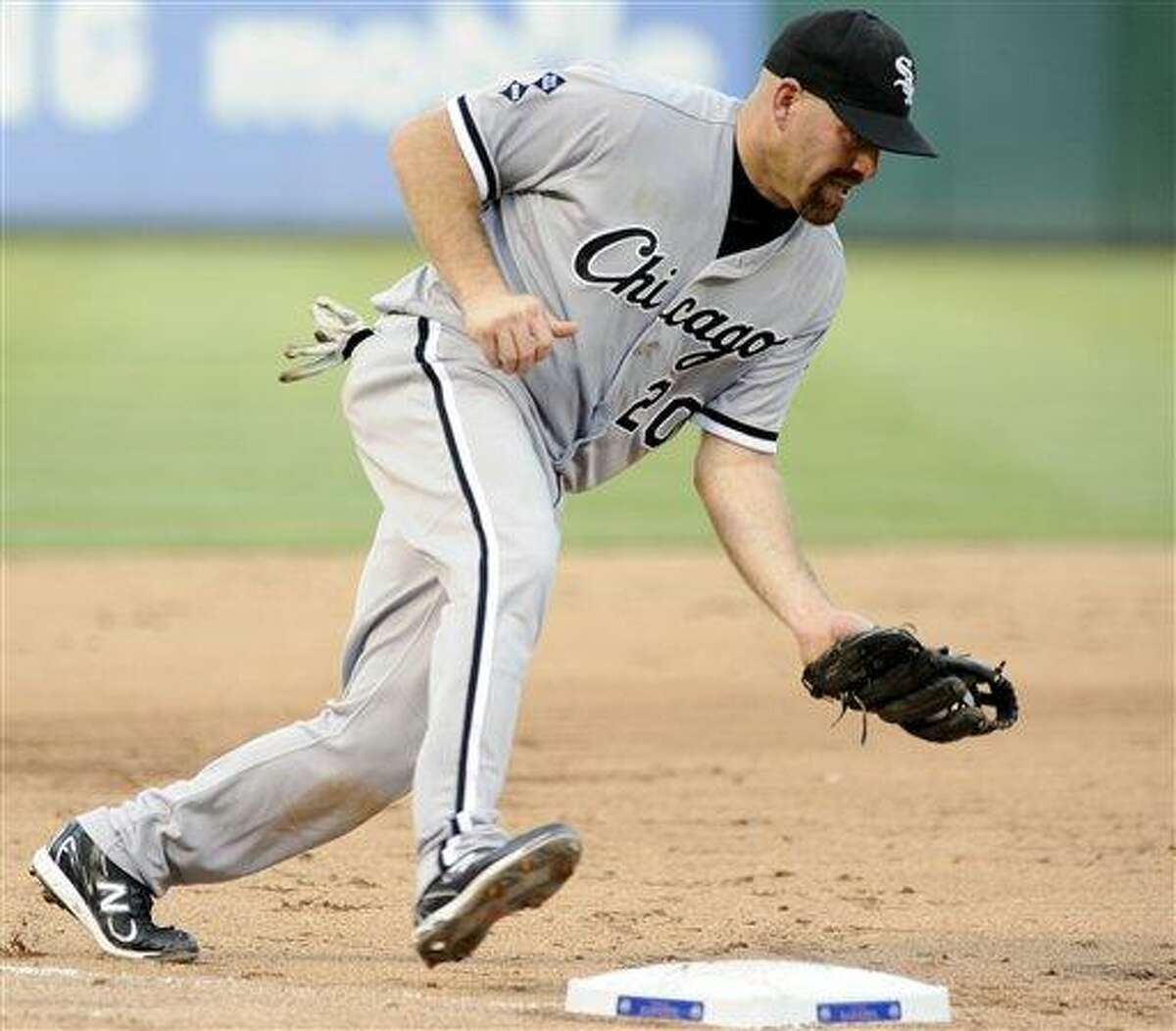 FILE - In this July 28, 2012, file photo, Chicago White Sox third baseman Kevin Youkilis (20) makes a play on the ball during a baseball game against the Texas Rangers in Arlington, Texas. A person familiar with the negotiations told The Associated Press Tuesday, Dec. 11, that free agent Youkilis and the New York Yankees have reached agreement on a $12 million, one-year deal. (AP Photo/Matt Strasen, File)