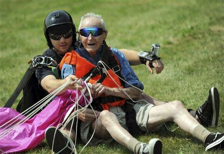 Lester Slate, 90, right, of Exeter, Maine, sits on the ground July 15 after his first skydiving jump made in tandem with instructor Matt Riendeau, left, at Central Maine Skydiving in Pittsfield, Maine. Associated Press/Bangor Daily News, Kevin Bennett Photo: AP / Bangor Daily News