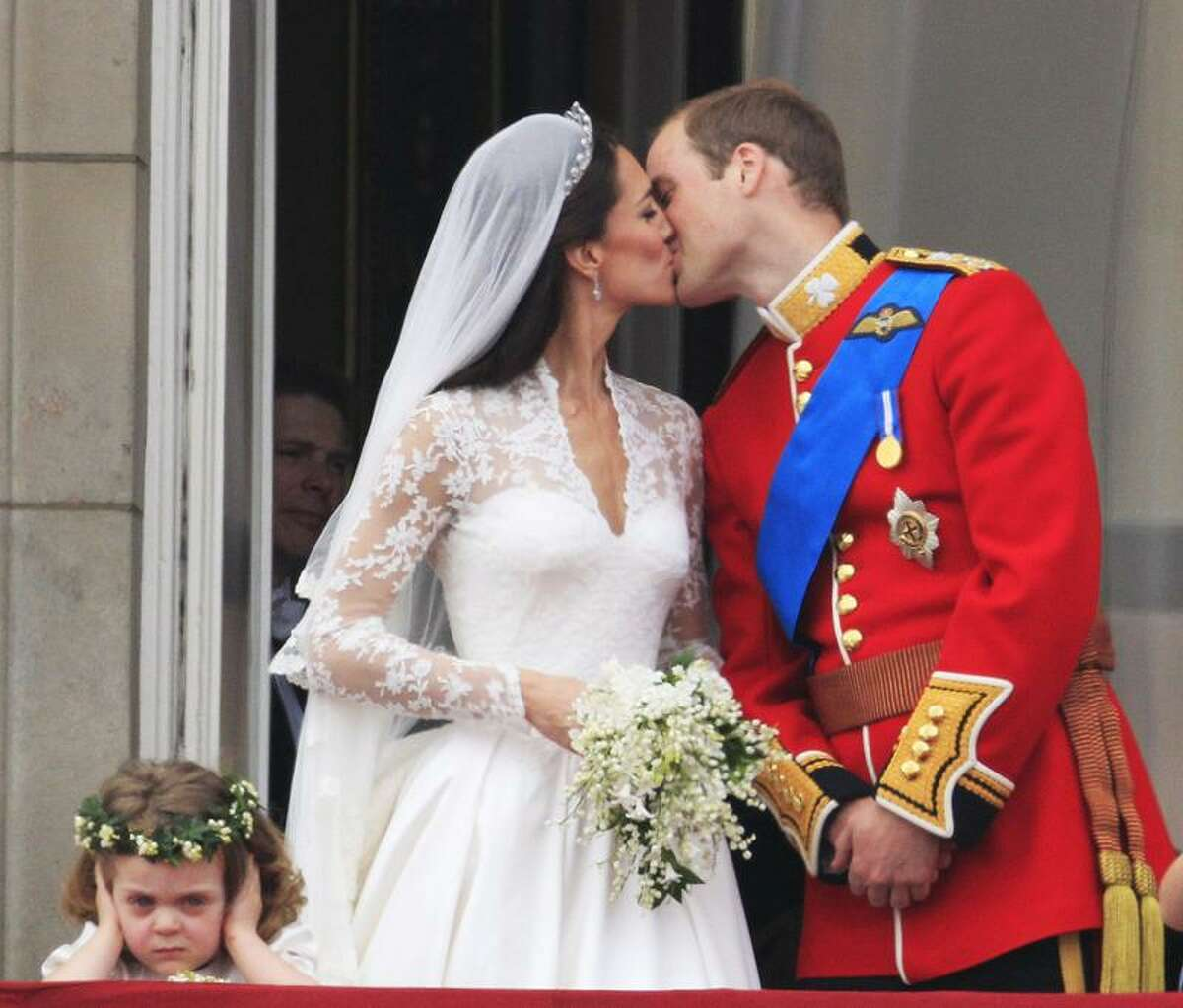 As bridesmaid Grace van Cutsem, left, covers her ears to shield herself from the sound of a Royal Air Force flyover, Britain's Prince William kisses his wife, Kate, Duchess of Cambridge, on the balcony of Buckingham Palace after the Royal Wedding in London Friday. Associated Press