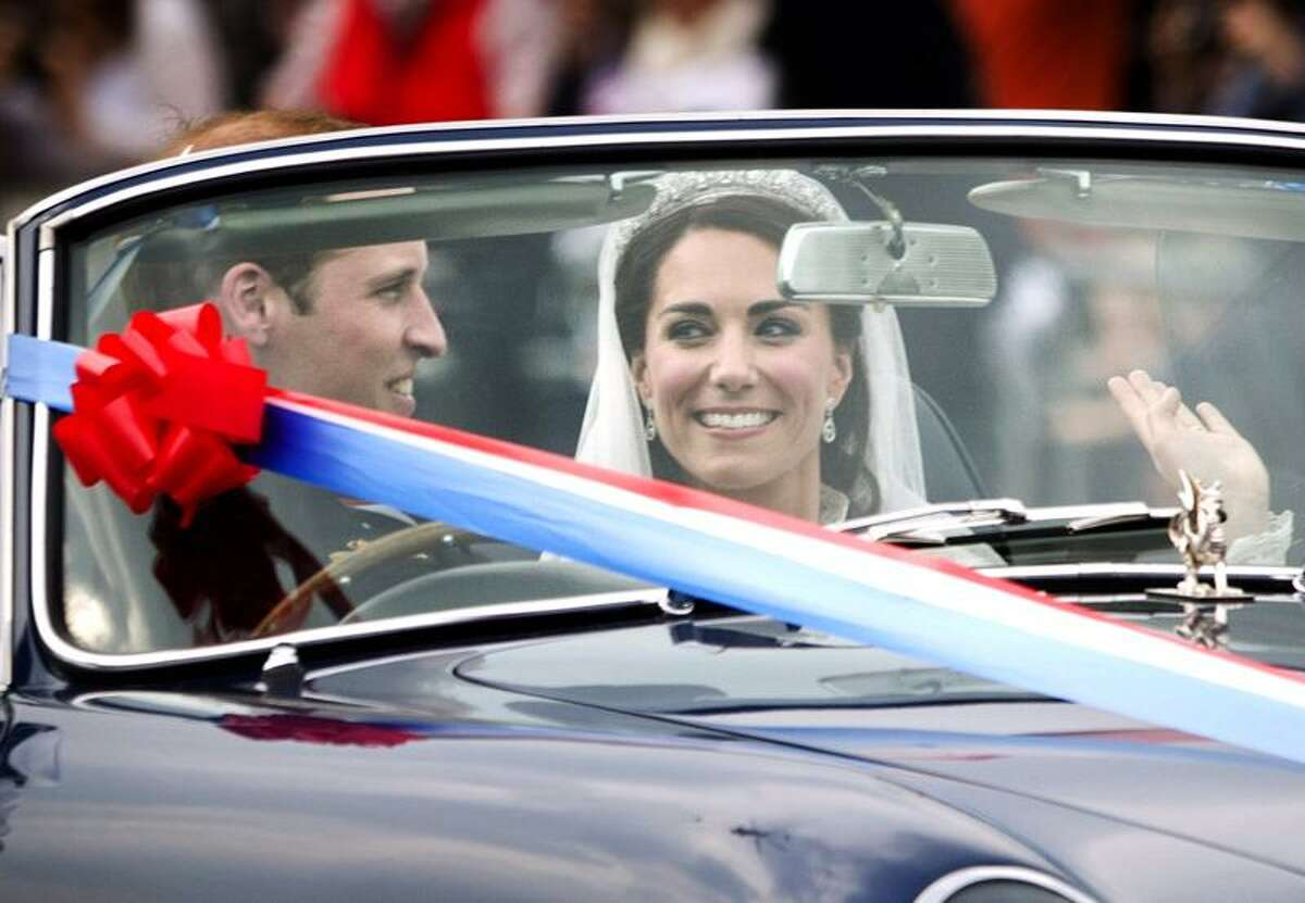 Prince William drives his new wife, Kate, Duchess of Cambridge, away from Buckingham Palace in a vintage Aston Martin Volante convertible after their wedding Friday. Associated Press