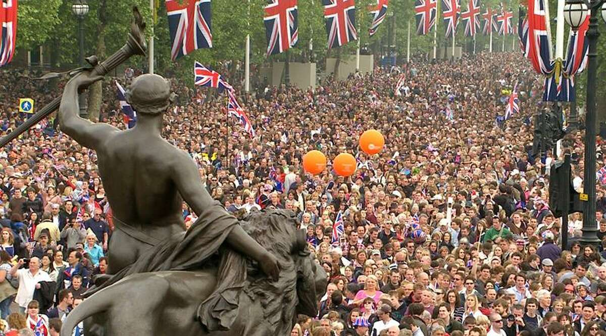 The crowd moves down the Mall, toward Buckingham Palace to watch a kiss between Prince William and Kate. Associated Press