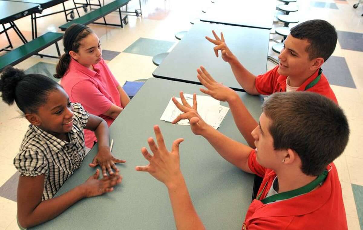 John G. Prendergast School fourth-graders Alisha Napoleon, front left, and Kaylya Ortiz get help with math earlier this week from Emmett O'Brien Technical High School sophomores Matt Himila, front, and Jeremy Rosa. Peter Casolino/Register