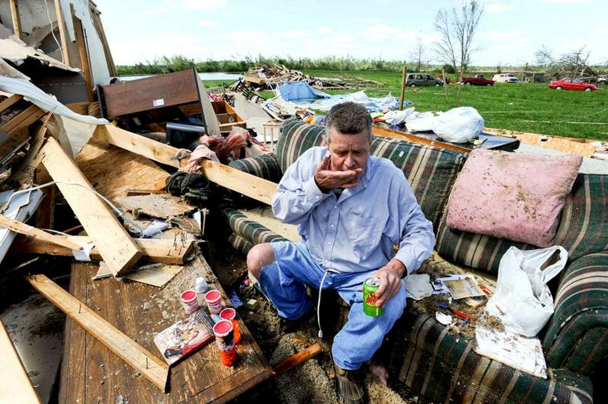 Billy Hughey sits in what is left of his living room floor Thursday, after it was destroyed by Wednesday's tornado near Tanner, Ala.