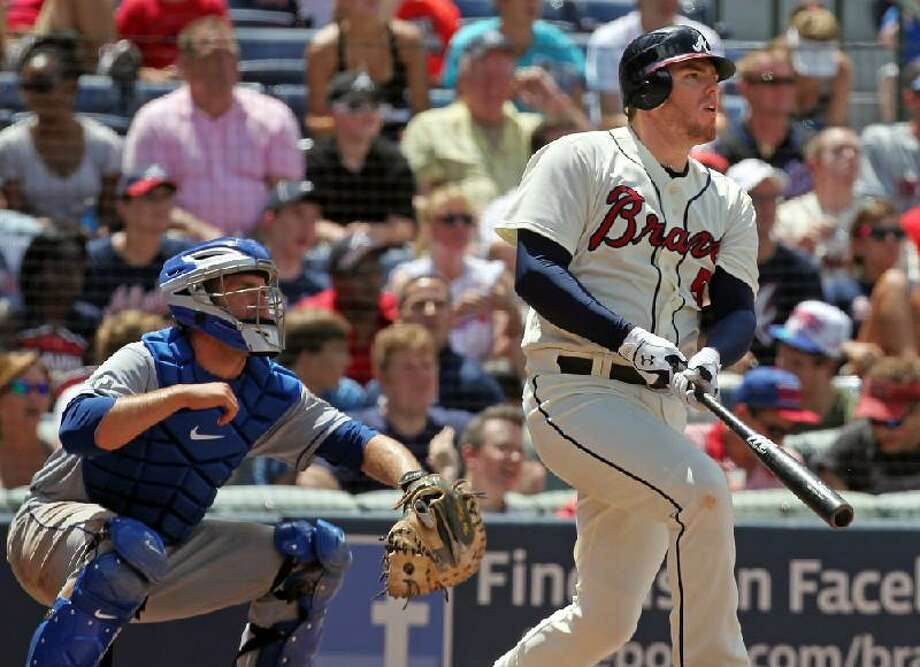 ASSOCIATED PRESS Atlanta Braves' Freddie Freeman hits a three-run homer as New York Mets catcher Josh Thole, left, watches during the fifth inning of Sunday's game in Atlanta. The Mets lost 6-1.