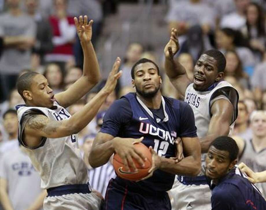 Connecticut's Andre Drummond, center, grabs the rebound during the first half of an NCAA college basketball game against Georgetown, Wednesday, Feb. 1, 2012, in Washington. Georgetown's Greg Whittington, left, and Henry Sims, top right, defend. (AP Photo/Haraz Ghanbari) Photo: AP / AP2012