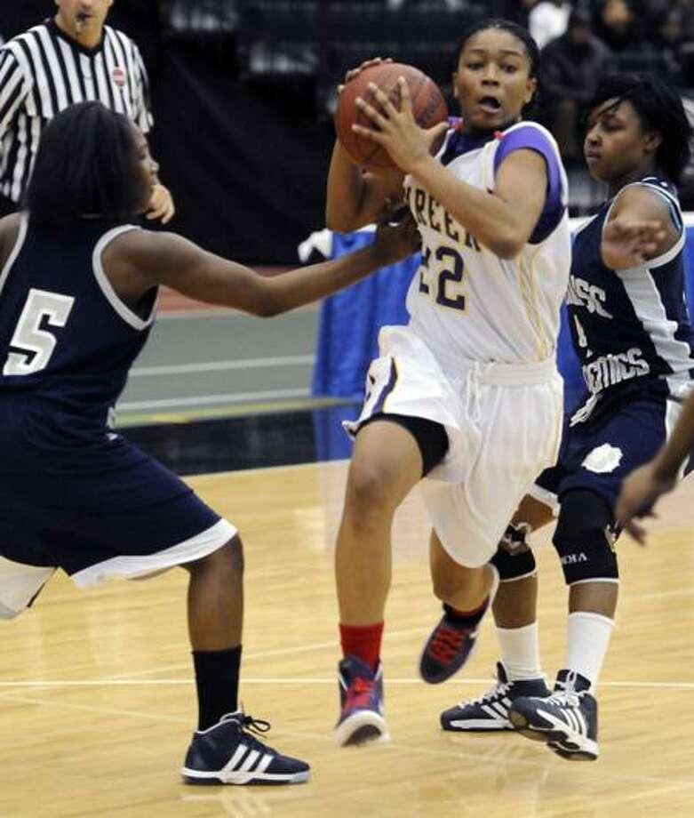 Career's Tanaya Atkinson splits between Hillhouse defenders Amber Lomax left and Michaela Frazier during Career's 59-42 win. Photo by Mara Lavitt/New Haven Register