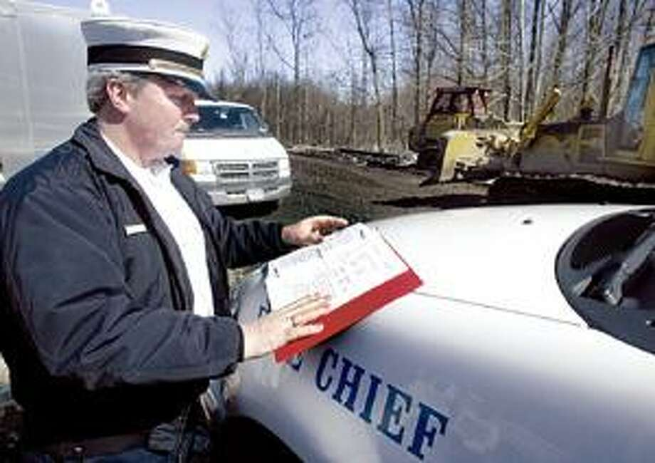 Photo by JOHN HAEGER Oneida Fire Chief Don Hudson looks over the disaster plan as clean up continues at the site of the March 12 CSX derailment on Tuesday, March 20, 2007.