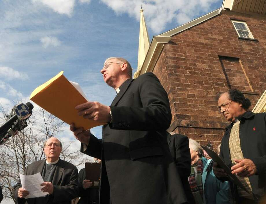 The Rev. Thomas Sievel of St. Vincent de Paul Roman Catholic Church speaks during a press conference called by East Haven clergy Wednesday at the Old Stone Church, United Church of Christ, in East Haven. / PETER HVIZDAK