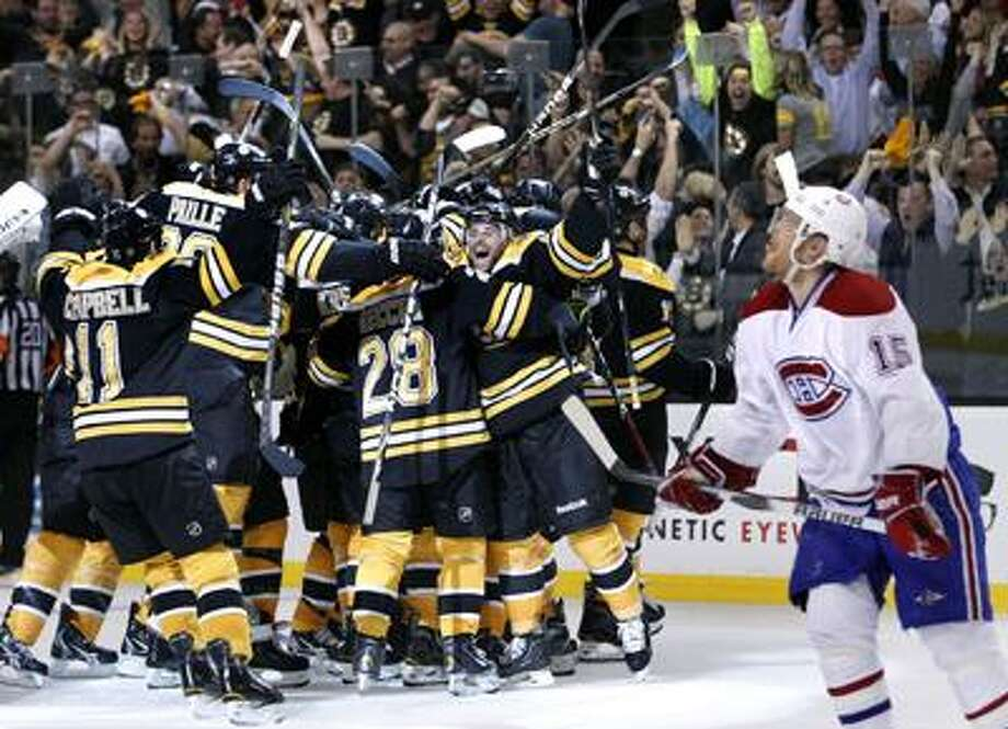 Montreal Canadiens center Jeff Halpern (15) looks up as Boston Bruins players celebrate the game-winning goal by Nathan Horton during the overtime period of Game 7 in a first-round NHL Stanley Cup hockey playoff series in Boston Wednesday, April 27, 2011. The Bruins won 4-3 to win the series. (AP Photo/Elise Amendola) Photo: AP / AP