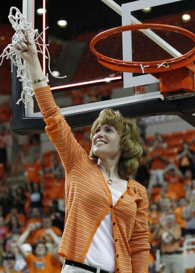 Shelley Budke, the widow of Kurt Budke, the Oklahoma State women's basketball coach who died in a plane crash in November of 2011, looks to the sky and raises the net after Oklahoma State defeated James Madison 75-68 in the WNIT Championship basketball game in Stillwater, Okla., Saturday, March 31, 2012. (AP Photo/Sue Ogrocki) Photo: AP / AP