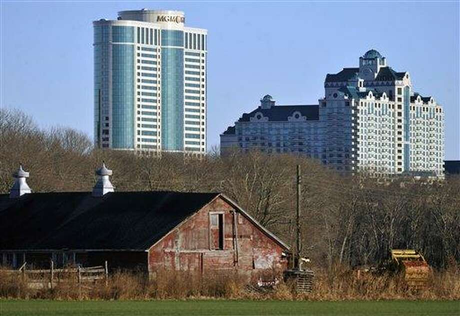 In this Nov. 11, 2012 file photo, Foxwoods Resorts Casino and MGM Grand at Foxwoods buildings loom behind a barn in Mashantucket, Conn.  Once one of America's wealthiest communities, the Mashantucket Pequot Indian reservation revived by the resort casino is reeling from a financial reversal that began in 2010.  (AP Photo/Jessica Hill) Photo: AP / AP2010