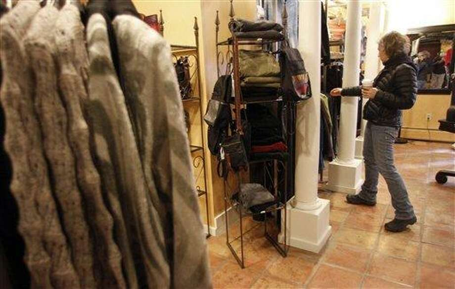 In this Feb. 28, 2012 file photo, Laurie Hanson looks over clothing at the Adorn clothing store in Montpelier, Vt. U.S. consumers boosted their spending in February by the most in seven months. But Americans' income barely grew, and the saving rate fell to its lowest point in more than two years, according to the Commerce Department. Associated Press Photo: AP / AP2012