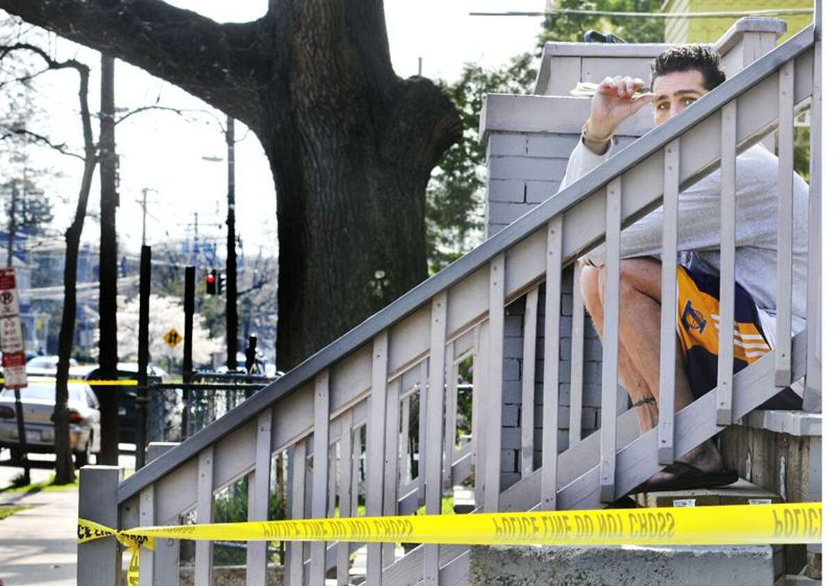 A witness of a double shooting Monday on Derby Avenue in New Haven says he was sitting on the steps, holding a child, when the shooting took place. He did not wish to be identified. (Melanie Stengel/Register)