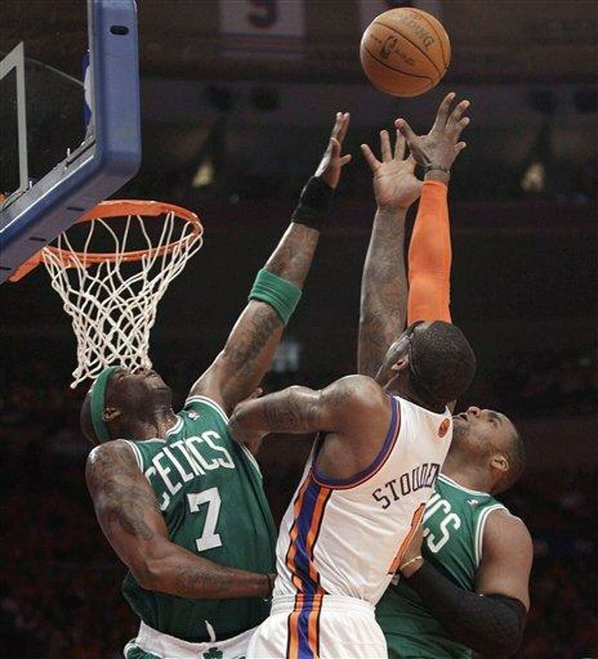 Boston Celtics center Jermaine O'Neal (7) and forward Glen Davis, right, go up for a rebound with New York Knicks forward Amare Stoudemire (1) in the first half of Game 4 of a first-round NBA basketball playoff series at Madison Square Garden in New York, Sunday, April 24, 2011. (AP Photo/Kathy Willens)