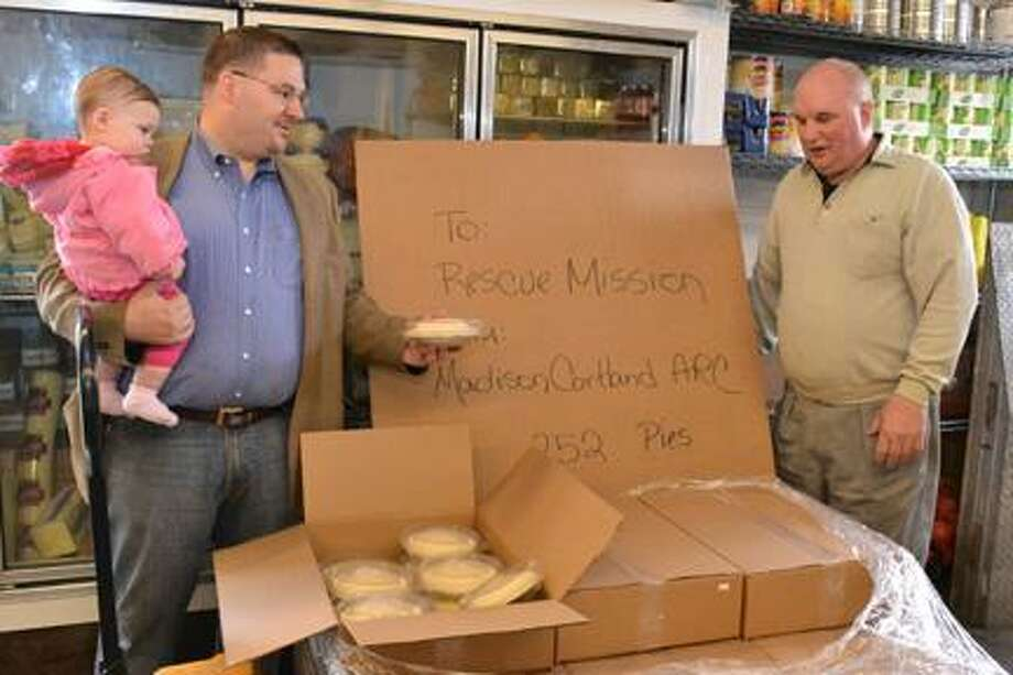 Submitted Photo From left, Bob Andrews, Manager of Business Development for Alternatives Industry at Madison Cortland ARC holding his daughter Jessica and delivers pies to Bob Purtell, Food Services Manager at the Rescue Mission. / MCARC Oneida NY