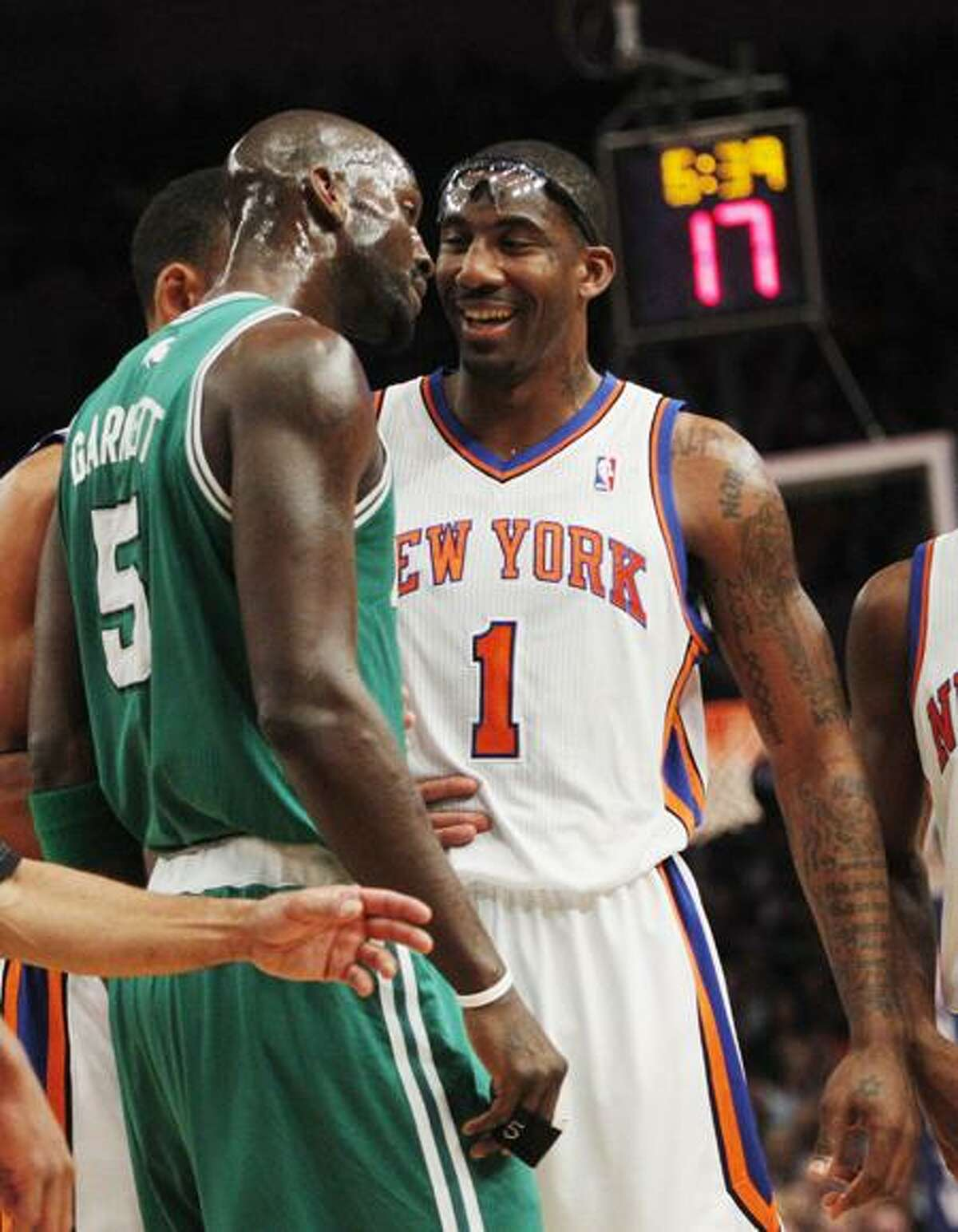 Boston Celtics' Kevin Garnett (5) exchanges words with New York Knicks' Amare Stoudemire (1) during the first half of Game 3 of a first-round NBA basketball playoff series Friday, April 22, 2011, in New York. (AP Photo/Frank Franklin II)