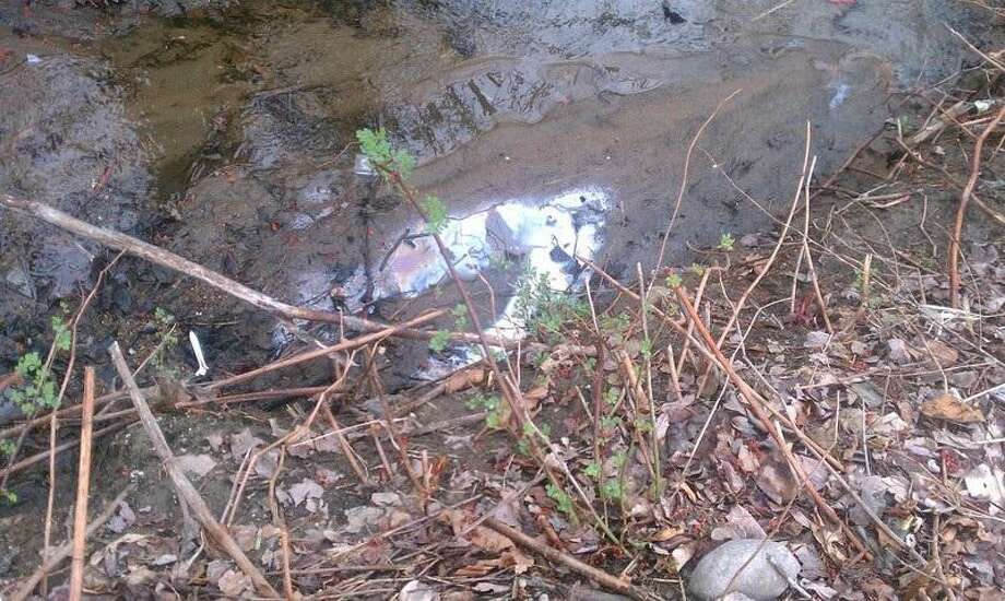 This photo was posted to SeeClickFix by a West Haven resident who wants the oil and debris cleaned from the brook near their home.