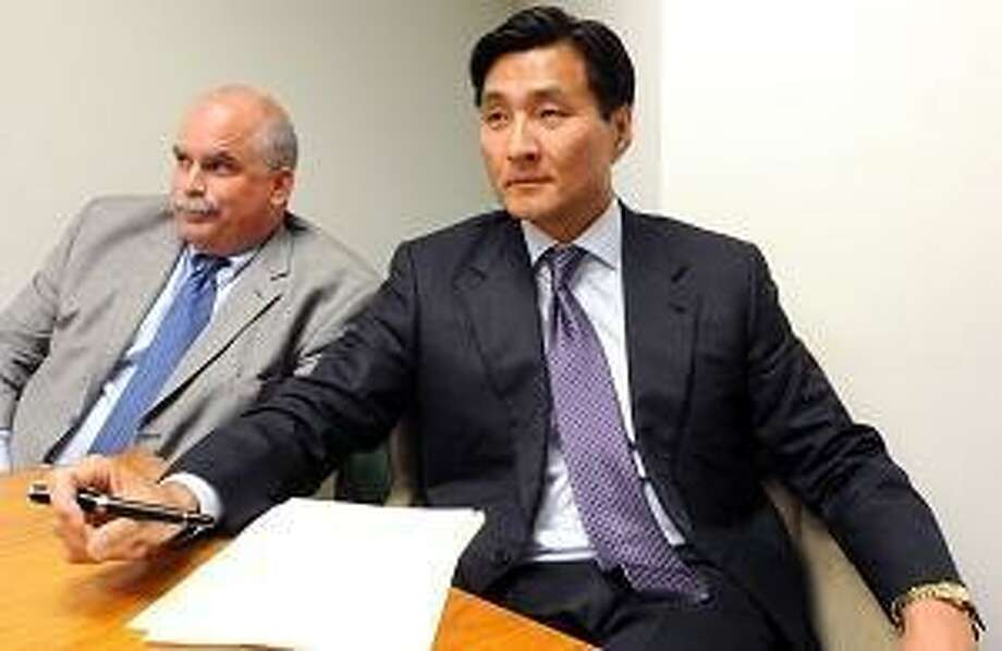 Charles Tiernan (left) sits with his client, Sung Ho Hwang, an attorney in New Haven, carried a gun legally into a New Haven movie theater on 8/7/12. Mara Lavitt/New Haven Register  8/8/12