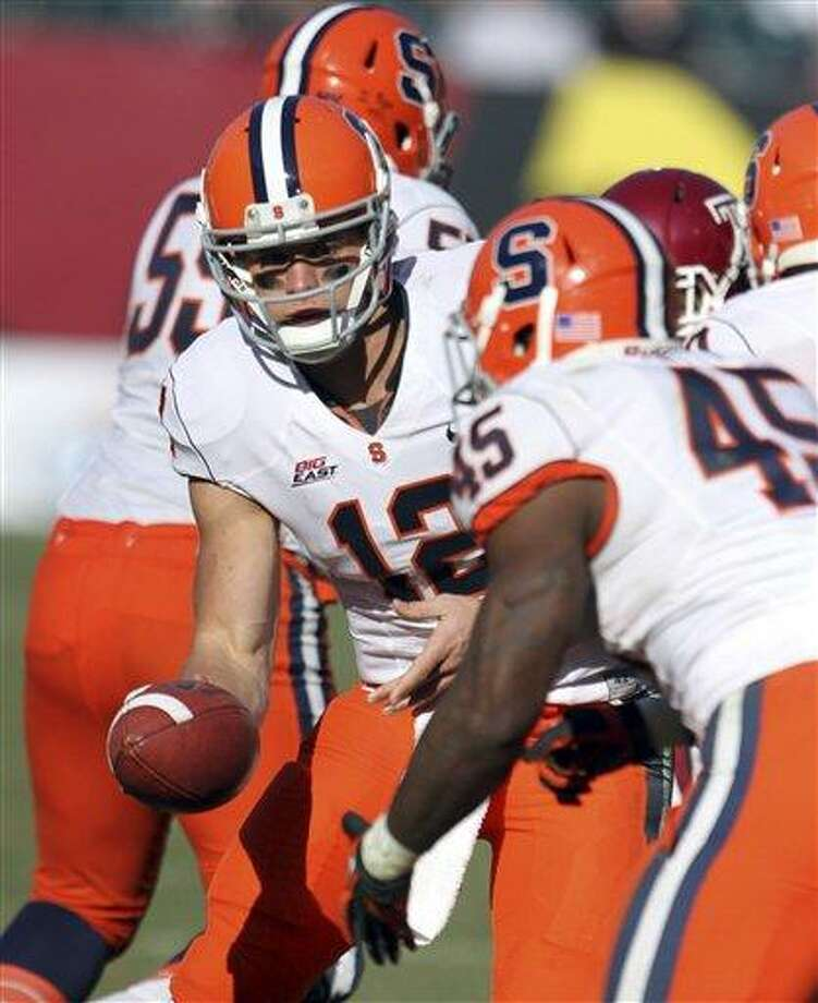 AP Photo Syracuse's Ryan Nassib (12) hands off to Jerome Smith (45) during the second half of a game against Temple. Photo: AP / The Philadelphia Inquirer