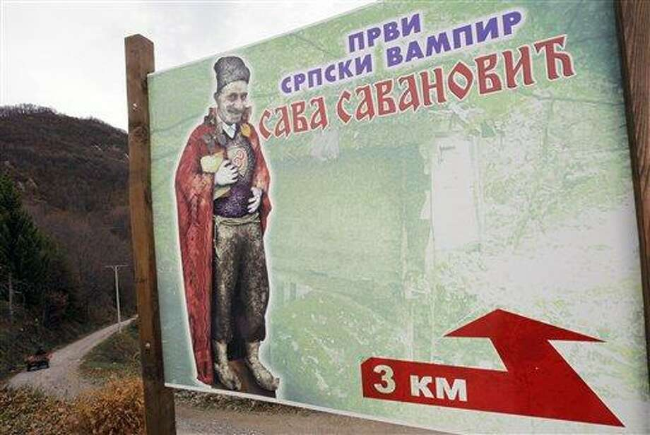 """In this Nov. 30 photo, a billboard near the village of Zarozje shows an artist's impression of the legendary vampire Sava Savanovic. The text reads: """"First Serbian vampire."""" Residents, who seem to half-believe that the legendary spook is back, have been advised to carry garlic, crosses and wooden stakes, just in case.  (AP Photo/Darko Vojinovic) Photo: AP / AP"""