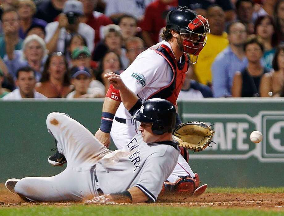 New York Yankees Jayson Nix (L) slides safely into home plate in front of Boston Red Sox catcher Jarrod Saltalamacchia during the second inning of American League MLB baseball action at Fenway Park in Boston, Massachusetts July 8, 2012. REUTERS/Jessica Rinaldi (UNITED STATES - Tags: SPORT BASEBALL) Photo: Reuters / X01704