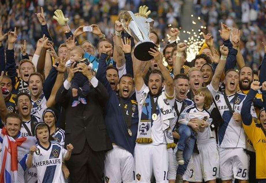 Los Angeles Galax's Landon Donovan hoist the trophy as they celebrate after defeating the Houston Dynamo 3-1 in the MLS Cup championship soccer game, Saturday, Dec. 1, 2012, in Carson, Calif. AP Photo/Mark J. Terrill) Photo: AP / AP