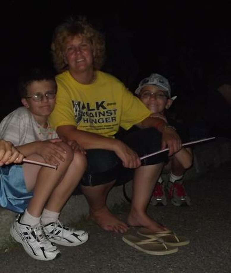 "RICKY CAMPBELL/Register Citizen Michael, Tracey and Anthony, all of Torrington, were seated on the curb closest to the baseball fields next to Torrington Middle School Saturday night prior to the fireworks show. ""We're excited,"" they all said before the show."