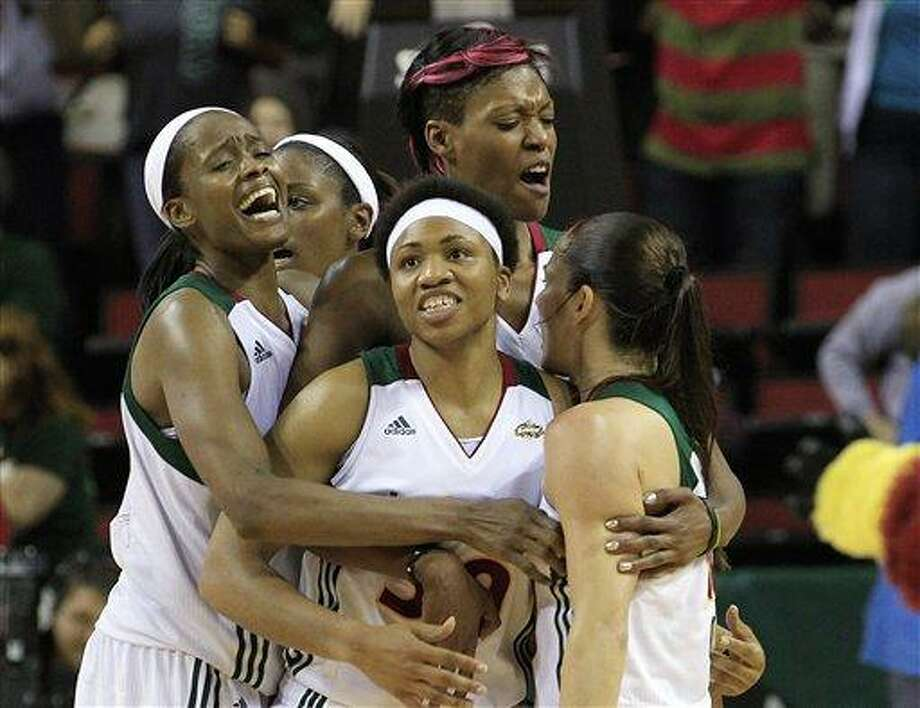 Seattle Storm's Sue Bird, right, is mobbed by teammates Swin Cash, left, Camille Little, Tanisha Wright, center front, and Ashley Robinson after Bird's game winning shot and the final buzzer against the Connecticut Sun in a WNBA basketball game Friday, Aug. 5, 2011, in Seattle. The Storm won 81-79, (AP Photo/Elaine Thompson) Photo: AP / AP