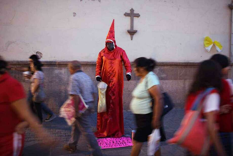 People walk past a street artist dressed as a magician performing for money by a church in the main square in Leon, Mexico, Thursday. Pope Benedict XVI will arrive in Mexico Friday, a decade after his predecessor's last visit, to a very different country and a church that has suffered debilitating setbacks amidst sex abuse scandals and a lower percentage of Mexicans who call themselves Catholic today, compared to a decade ago. Associated Press Photo: AP / AP