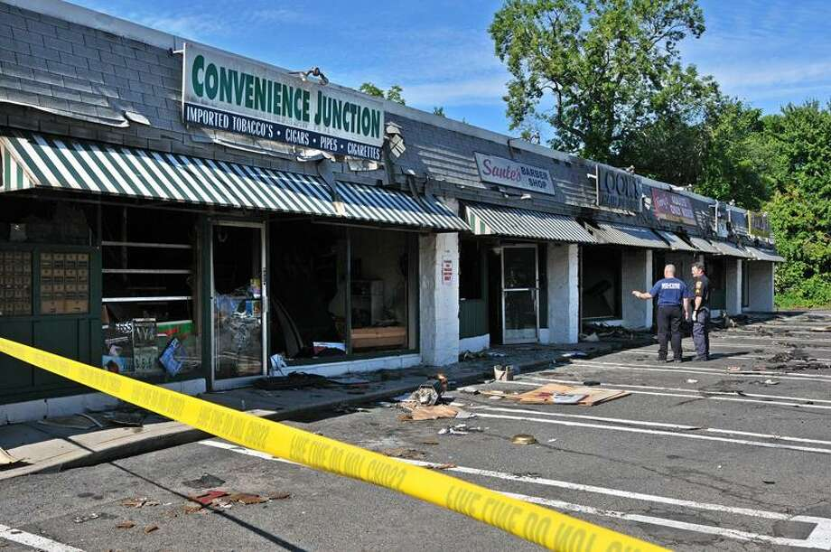Fire investigators work at 753-755 Boston Post Road in Milford Wednesday, after a three-alarm fire destroyed all but one business in a strip mall. Peter Casolino/Register