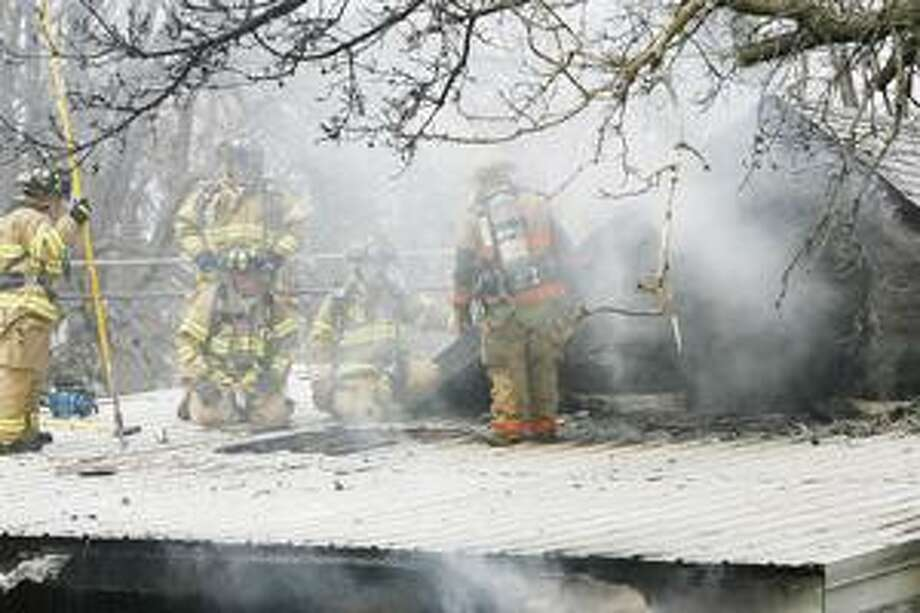 Photo by JOHN HAEGER Area fire crews battle a house fire on State Street in the Village of Canastota on Tuesday, April 12, 2011.