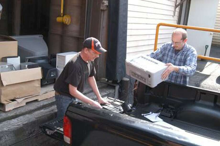 Dispatch Staff Photo by KURT WANFRIED Lojo Technologies staff members James Bouyea, left, and Chris Sandlass unload gear to be recycled Monday. The program  opens to the public April 18.