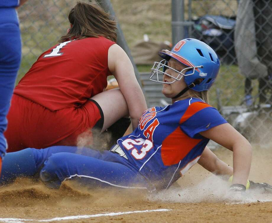 Dispatch Staff Photo by JOHN HAEGER Oneida's Jackie Cavanagh (23) slides into home on a wild pitch as Chittenango's Kaleigh Koegel(1) bobbles the throw in the bottom of the second inning of play  on Friday, April 8, 2011 in Oneida.