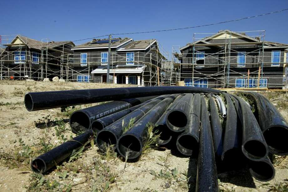 """PVC pipes are seen next to new single-family detached homes being built by Lennar at the """"Aria at West Creek"""" development in Santa Clarita, Calif.  U.S. builders started work on slightly fewer homes in February, but they began preparing for what could be the healthiest spring buying season since the housing bubble burst. (AP Photo/Damian Dovarganes) Photo: AP / AP2012"""