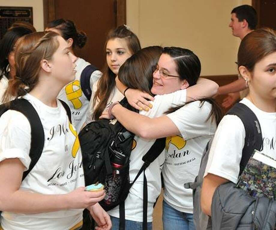 Hamden High students Taylor Jacques (facing camera) hugs Stephanie Notaro as students  gathered in the lobby for a photo to send to fellow senior, Jordan Jaques, a student battling cancer. Jordan Jaques is at Mass General this week undergoing surgery in his battle with cancer. Taylor Jacques is Jordan's twin brother and she designed the tee shirts her fellow students are wearing. (Photo by Peter Casolino/New Haven Register)