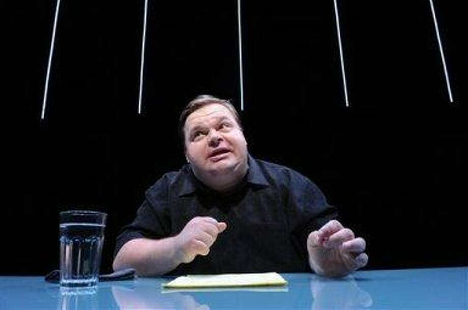 """In this undated image released by The Public Theater, Mike Daisey is shown in a scene from """"The Agony and The Ecstasy of Steve Jobs,"""" in New York. Daisey, whose latest show has been being credited with sparking probes into how Apple's high-tech devices are made, is finding himself under fire for distorting the truth. The public radio show """"This American Life"""" retracted a story Friday, March 16, 2012, that it broadcast in January about what Daisey said he saw while visiting a factory in China where iPads and iPhones are made. (AP Photo/The Public Theater, Stan Barouh)"""