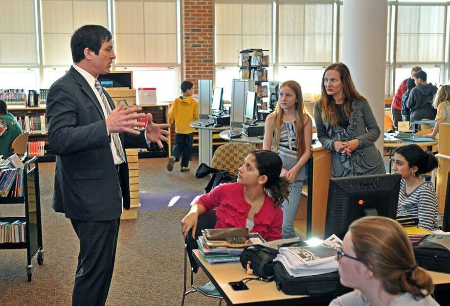 """Kevin J. Paul, a financial adviser with Edward Jones in Cheshire, talks to students at Wintergreen Interdistrict Magnet School in Hamden about funding options for a theme restaurant they are working on called """"We Are the World.""""   Peter Casolino/New Haven Register"""