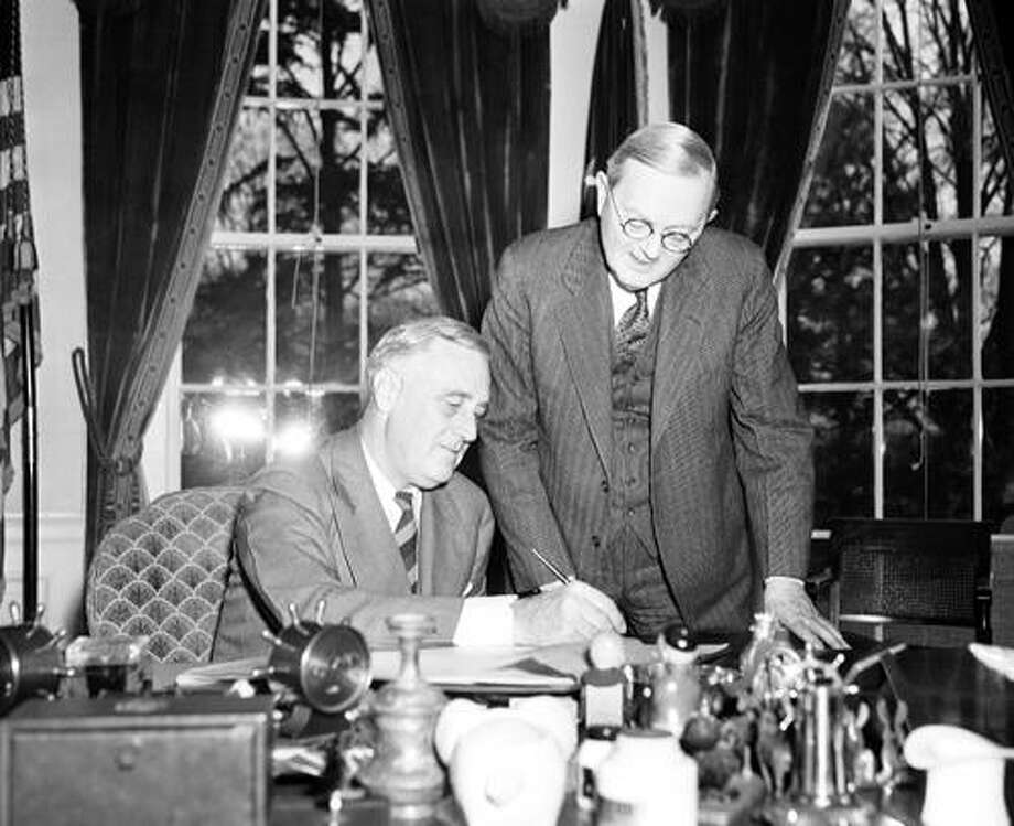 FILE - In this April 2, 1940 file photo, William L. Austin, director of the U.S. Census Bureau, right, helps President Franklin D. Roosevelt fill out the large form at the White House in Washington. Veiled in secrecy for 72 years because of privacy protections, the 1940 U.S. Census is the first historical federal decennial survey to be made available on the Internet initially rather than on microfilm. (AP Photo) Photo: ASSOCIATED PRESS / AP1940