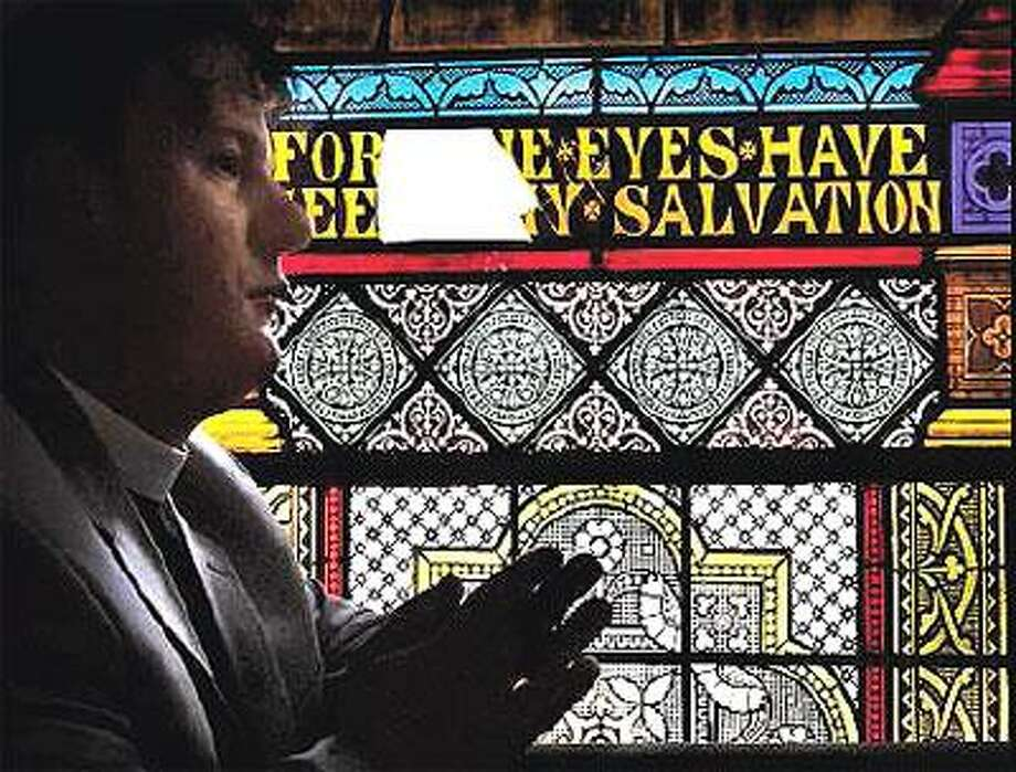 The Rev. Alex Dyer stands near one of the damaged stained glass windows at St. Paul & St. James Episcopal Church in New Haven. (Melanie Stengel/Register)