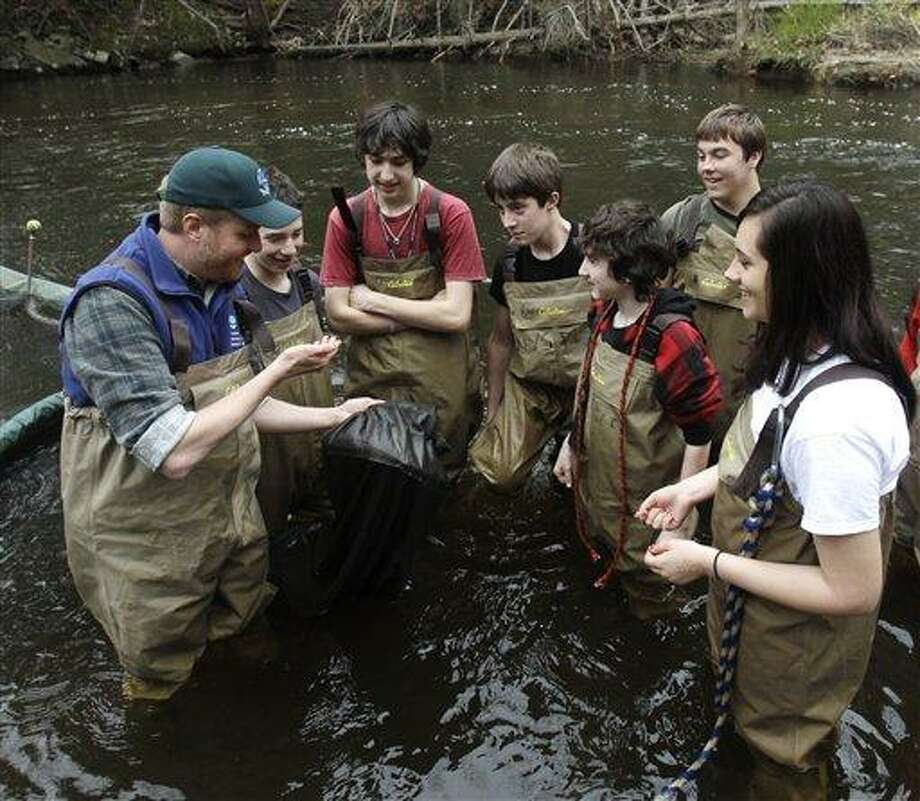 In this April 2011 file photo, Chris Bowser of the New York State Department of Environmental Conservation, left, checks a net for American eels with Kingston High School students on the Black Creek in West Park, N.Y. They have a reputation for being environmentally minded do-gooders. But an academic analysis of surveys spanning more than 40 years has found that today's young Americans are less interested in the environment and in conserving resources - and often less civic-minded overall - than their elders were when they were young. Associated Press Photo: AP / AP2011