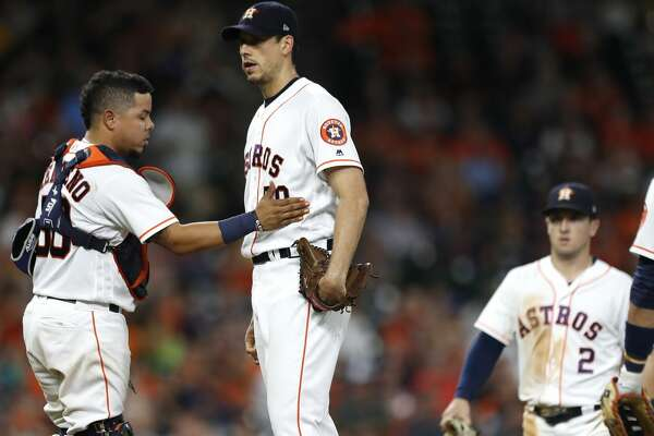 Houston Astros catcher Juan Centeno (30) pats starting pitcher Charlie Morton (50) as manager A.J. Hinch walks out to pull him during the seventh inning of an MLB game at Minute Maid Park, Wednesday, Aug. 16, 2017, in Houston.  ( Karen Warren / Houston Chronicle )