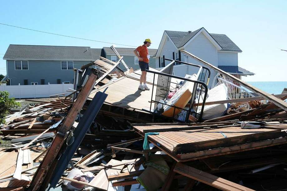 East Haven-- Andy Weinstein surveys whats left of his home on Cosey Beach Avenue in East Haven. 25 homes were destroyed by Hurricane Irene .  Peter Casolino/New Haven Register