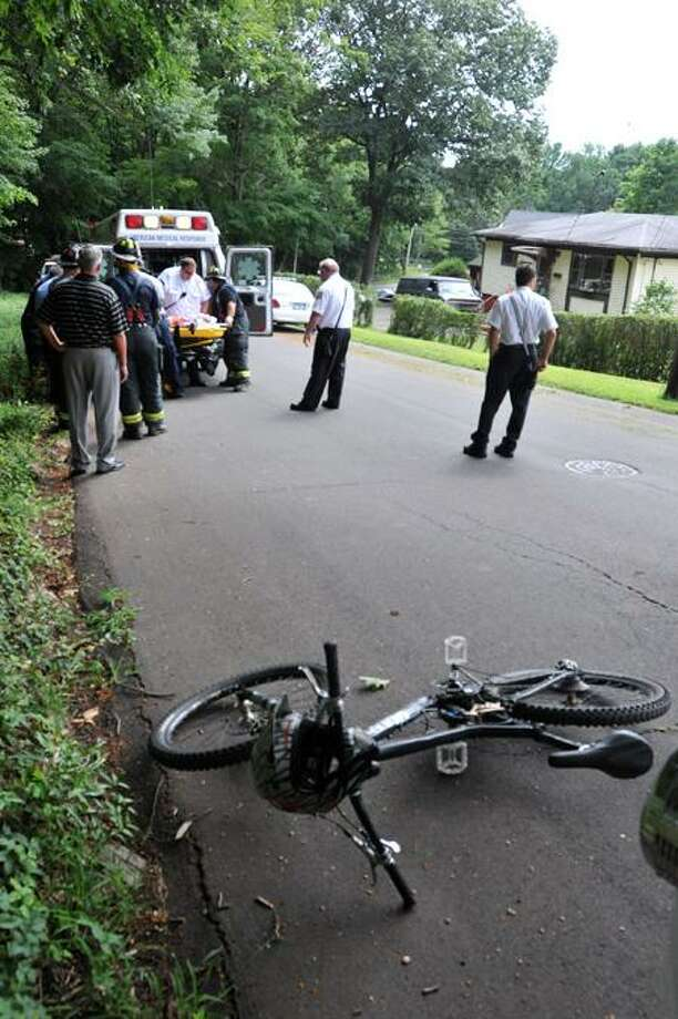 Emergency workers place a man in an ambulance on Rock Ridge Road at the bottom of West Rock State Park after he was injured cycling. Peter Casolino/New Haven Register