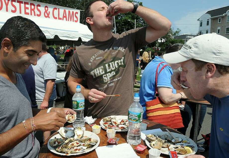 Roger Ayres of Milford, left; Shane Hemphill of Cary, N.C., center; and Kevin Kenneally of Milford, right, consume some of the offerings Saturday at Milford's 38th Annual Oyster Festival. Mara Lavitt/New Haven Register