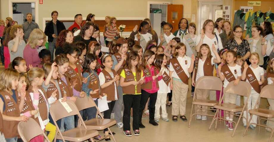 Girl Scouts at the Dunbar United Church of Christ in Hamden join Scouts across the nation in reciting the Girl Scout Promise as part of the 100th anniversary of the organization.  Reece Alvarez/Special to the Register