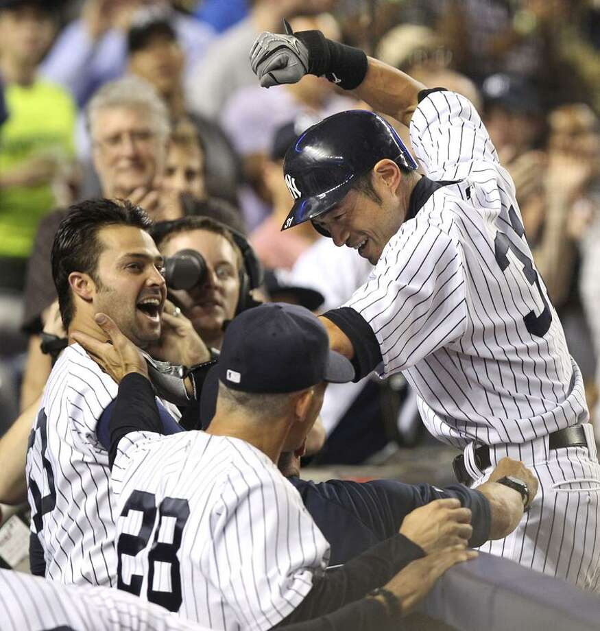 New York Yankees' Ichiro Suzuki, right, celebrates his second home run with Nick Swisher, left, and others as he returns to the dug out during the sixth inning of the baseball game against the Boston Red Sox Sunday, Aug. 19, 2012 at Yankee Stadium in New York.  (AP Photo/Seth Wenig) Photo: AP / AP