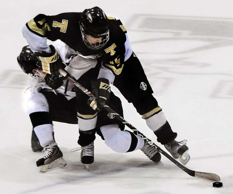 Guilford's Billy Ring, left, and Trumbull's Michael Ahearn fight for the pick at center ice during the second period of the semifinals of the Division II state tournament on Monday night at Yale's Ingalls Rink. (Melanie Stengel/Register)