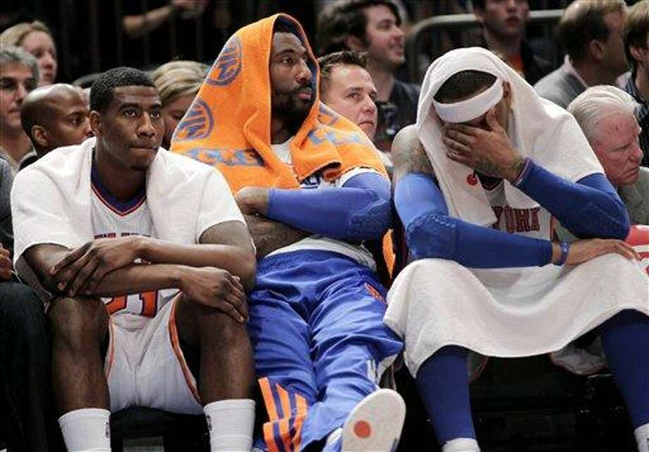New York Knicks' Iman Shumpert, left, Amare Stoudemire, center, and Carmelo Anthony sit on the bench toward the end of an NBA basketball game against the Philadelphia 76ers in New York, Sunday, March 11, 2012. The 76ers defeated the Knicks 106-94. (AP Photo/Seth Wenig) Photo: AP / AP