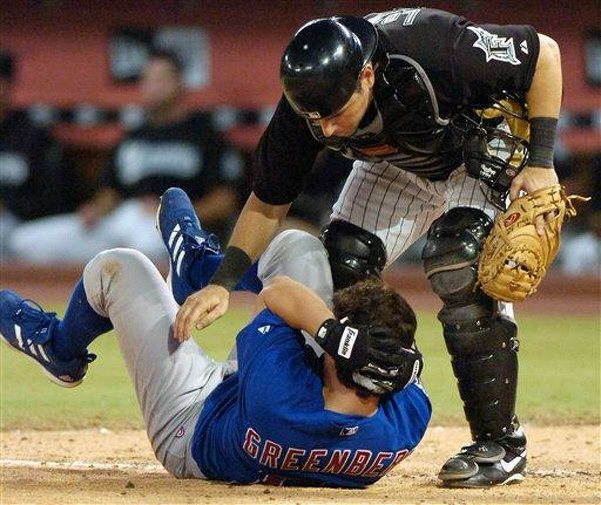 Florida Marlins catcher Paul Lo Duca rushes over to check on Chicago Cubs rookie Adam Greenberg of Guilford after Greenberg was hit in the helmet by the first pitch he faced in the major leagues, from Florida Marlins relief pitcher Valerio Do Los Santos during the ninth inning, July 9, 2005, in Miami. (AP Photo/Steve Mitchell)
