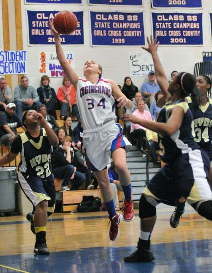 Durham--Coginchaug's Jessica Solomon drives past Hyde defenders during the first half. Photo- Peter Casolino/New Haven Register 03/08/12